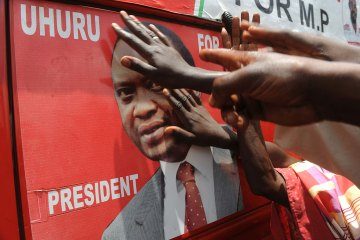 Supporters of Kenyan presidential candidate Uhuru Kenyatta touch his picture on an election poster as they celebrate upon learning of his victory in Kenya's national elections on March 9, 2013 in Kiambu, north of Nairobi.