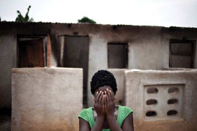 A woman hides her face after recounting how pro-Ouattara forces killed two of her children and her brother.© 2011 Peter Dicampo